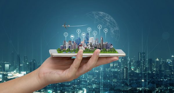 Smart city and Internet of things (IOT) on smartphone in hand, objects icon connecting together, Internet networking concept with background modern city blurred.